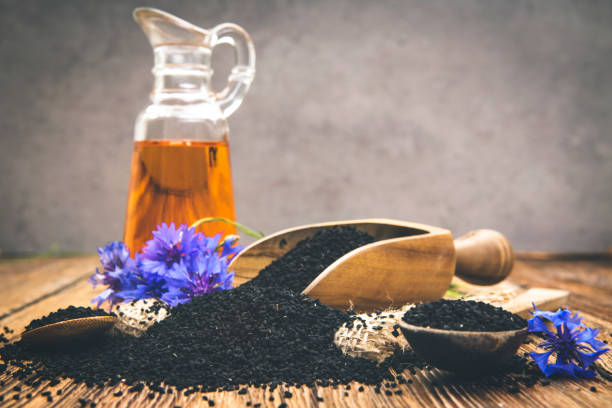 Nigella oil seeds and flower on wooden table with space